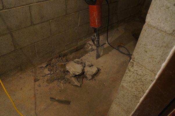 breaking concrete slab with jack hammer